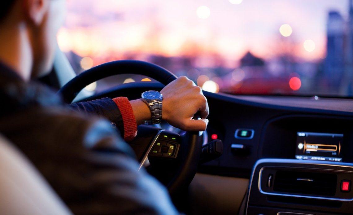 Homem no volante, aproveitando bem acessórios para carro como um som automotivo.