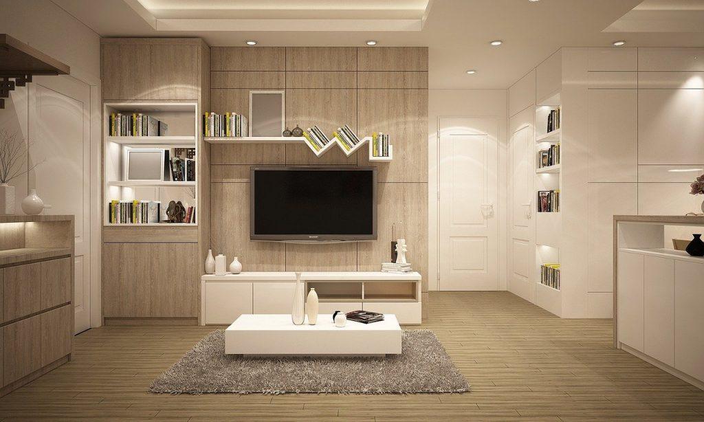 Há uma sala toda mobiliada com rack, painel, televisão, mesa de centro e muitos spots. Tudo perfeito em termos de iluminação para a sala.