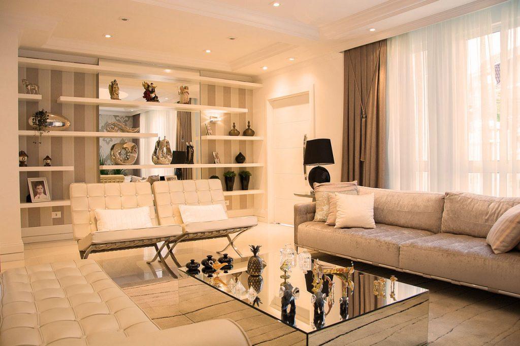Há uma sala com sofá creme, uma mesa de centro e spots led branco quente.