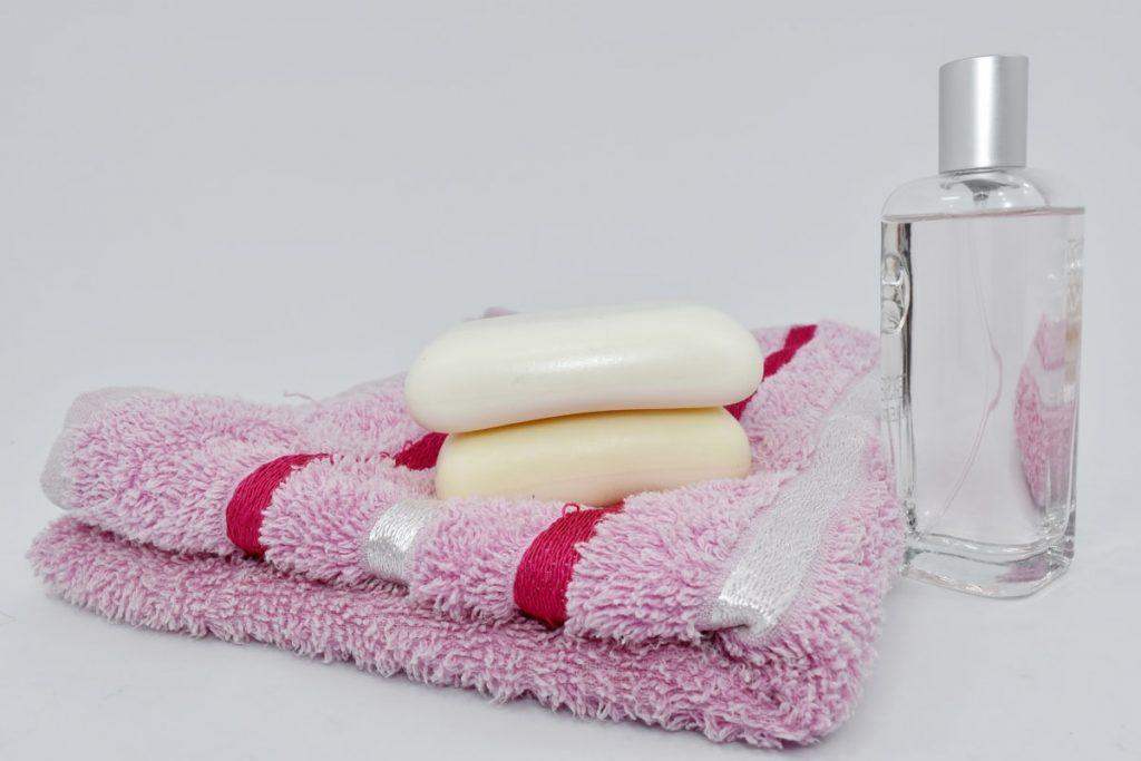 Toalha com dois sabonetes e um vidro de perfume,