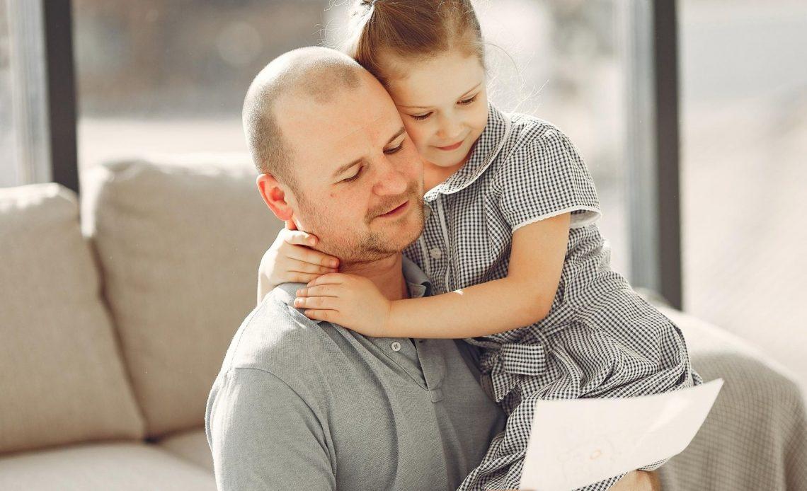 Pai abraçado com sua filha no sofá e segurando uma cartinha que ganhou de presente.