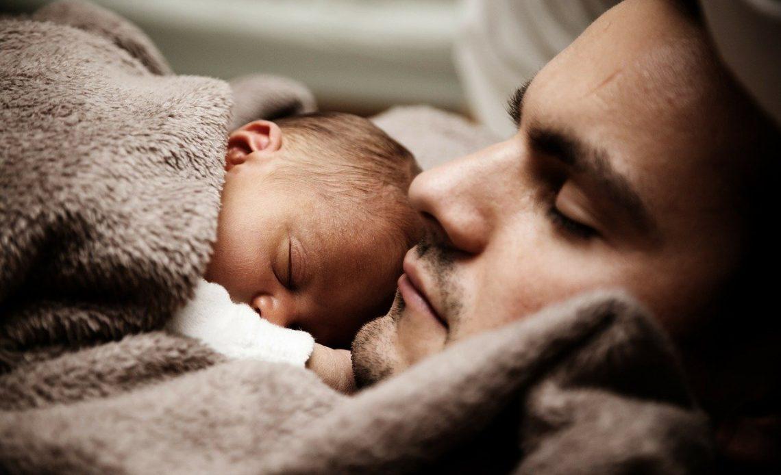 Na foto, bebê dorme próximo ao rosto do seu pai.
