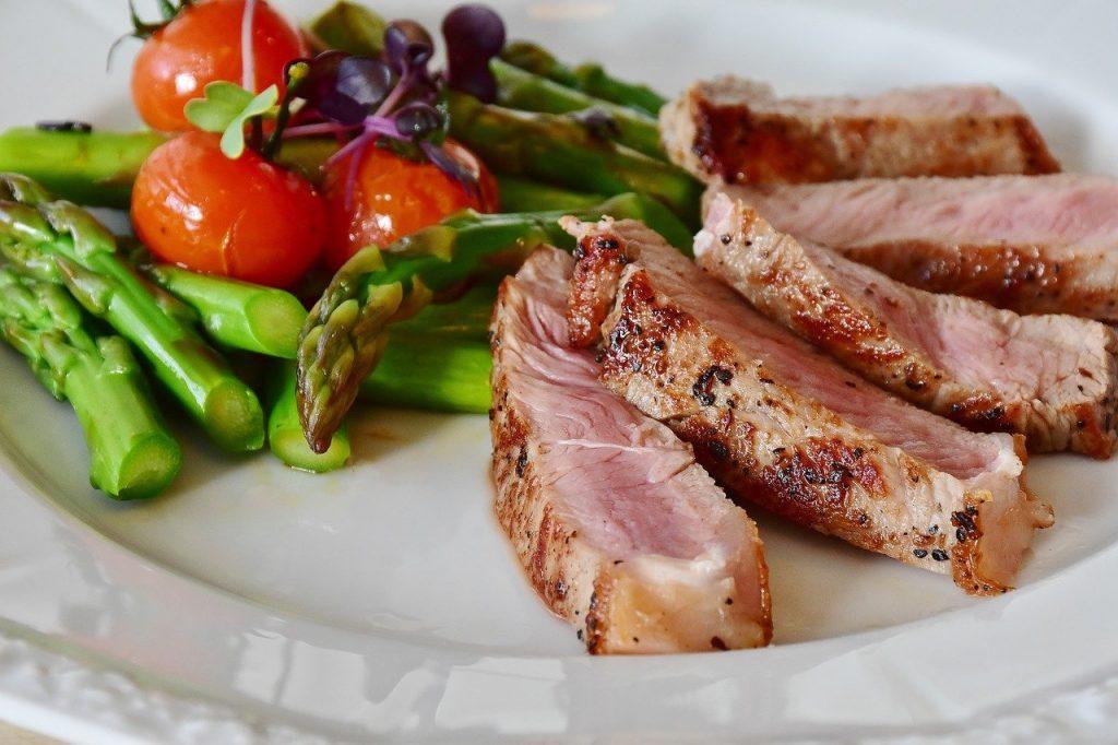 Salada de aspargos com tomate e fatias de carne de porco.