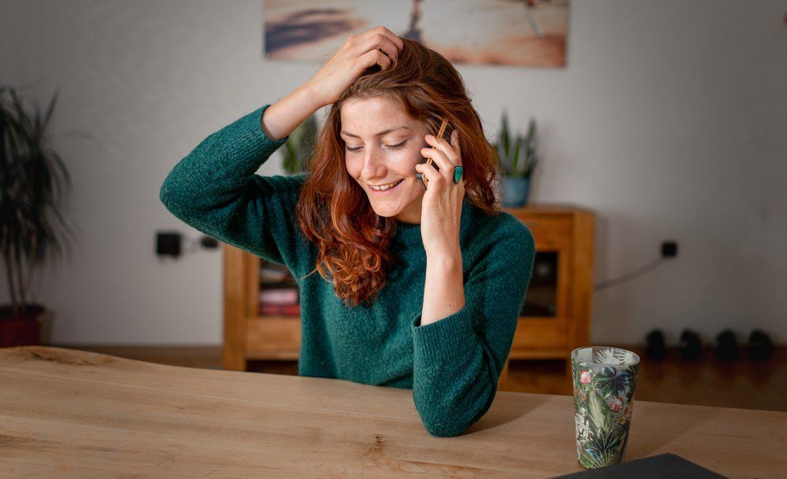 Mulher sorridente à mesa falando no celular.