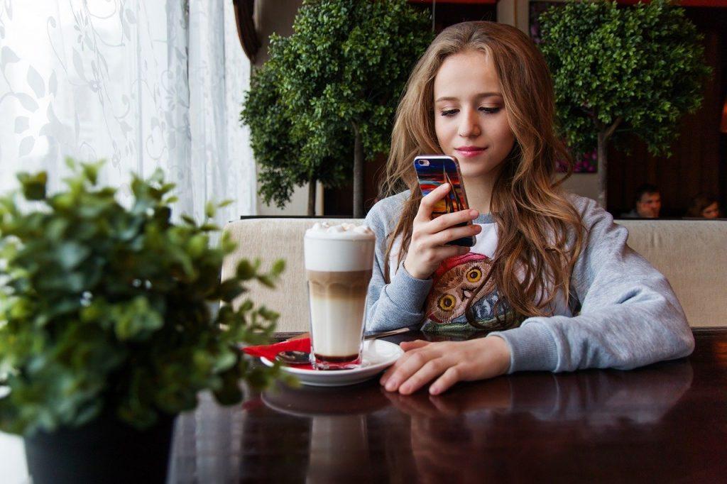 Mulher jovem e sorridente sentada à mesa, que contém uma xícara de café. Ela mexe no seu celular.
