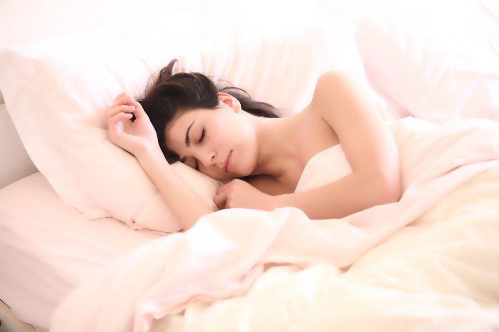 Mulher dormindo em sua cama e coberta.
