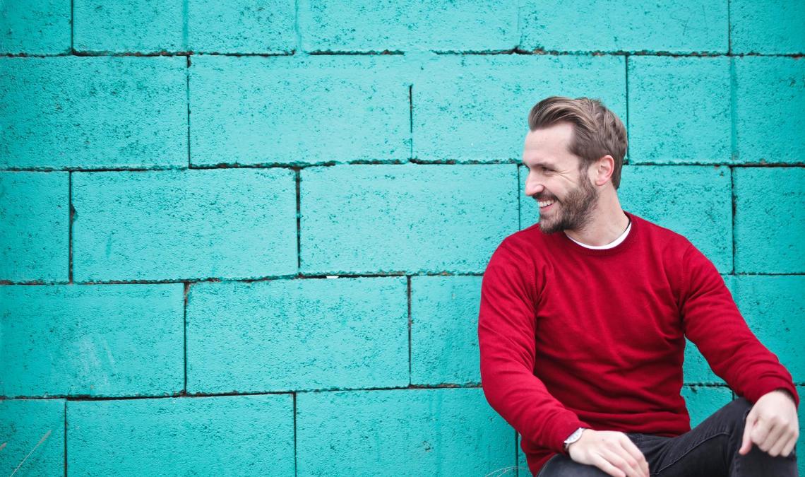 Homem sorridente, encostado na parede,