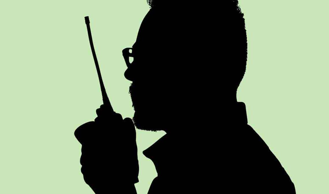 Sombra de homem falando em rádio comunicador.