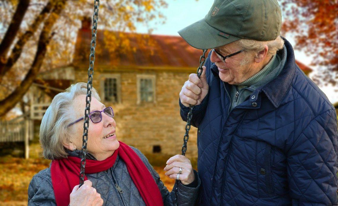 Casal de idosos. Uma senhora está em um balanço de parque, enquanto o seu marido sorri para ela.