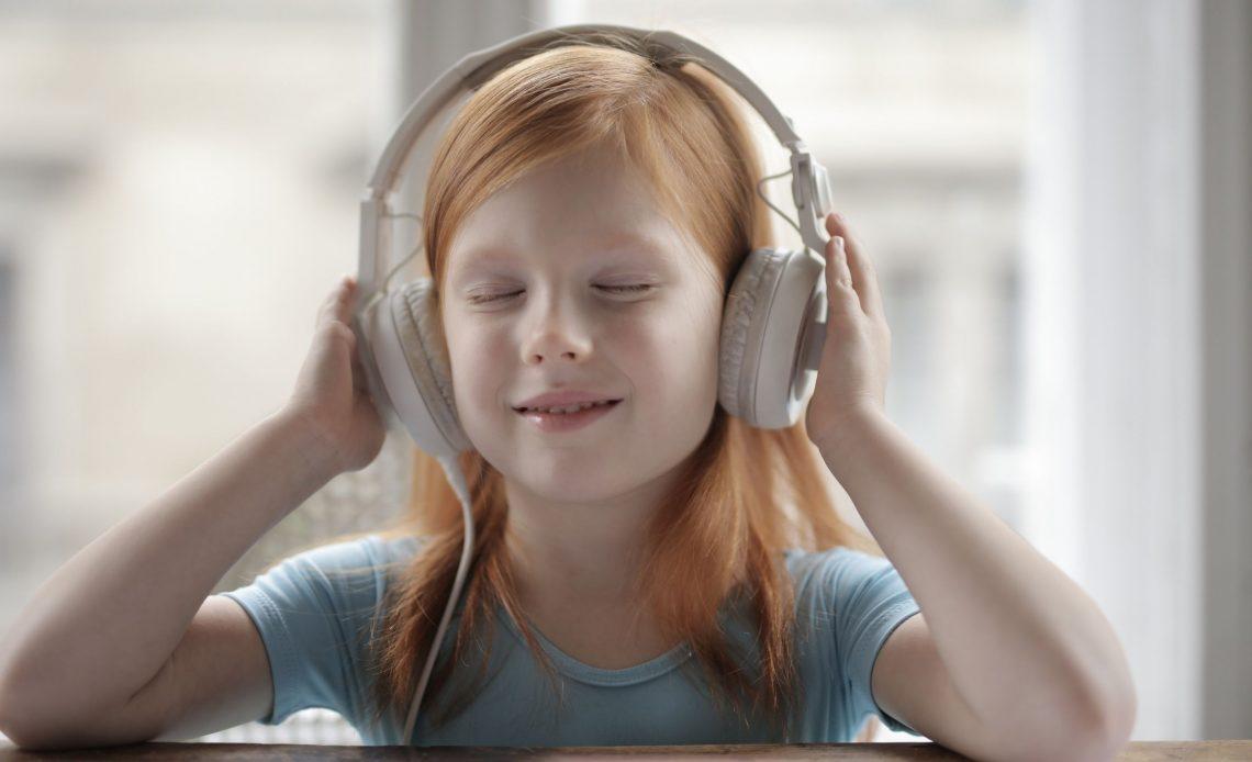 Menina com fone de ouvido headphone e olhos fechados.