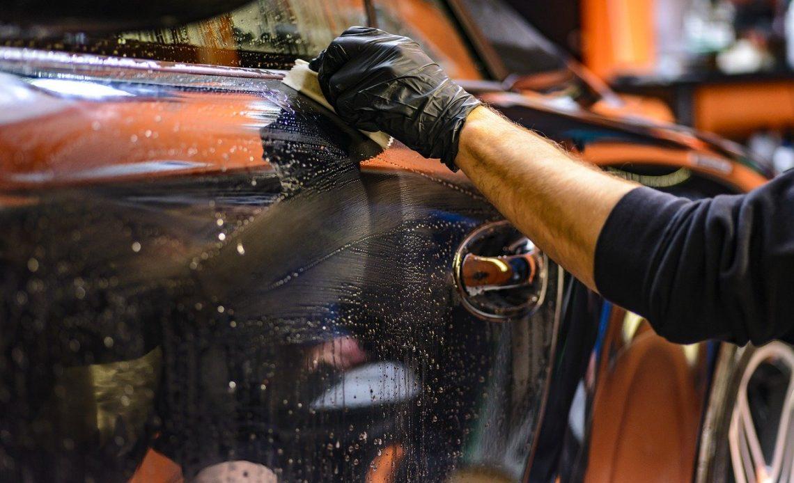 Na foto, há uma mão masculina limpando a lataria de um carro.