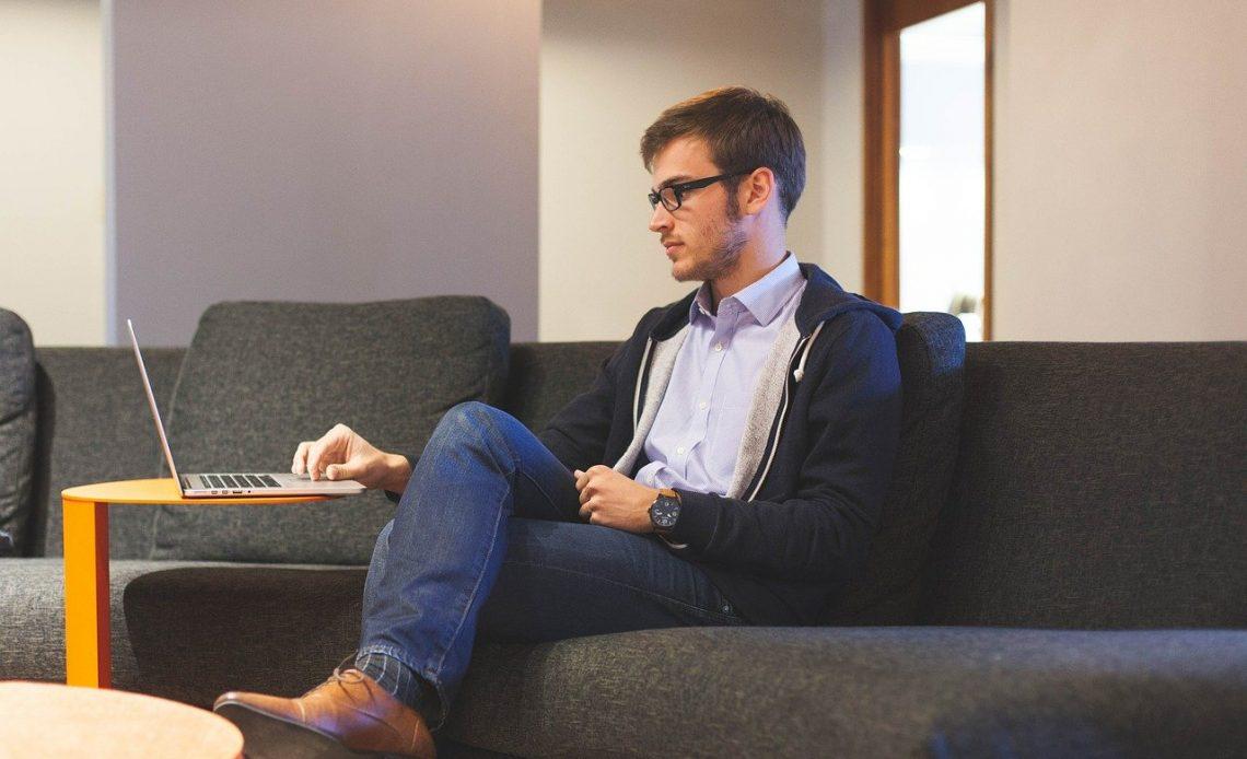 Homem sentado ao sofá enquanto mexe no seu notebook.