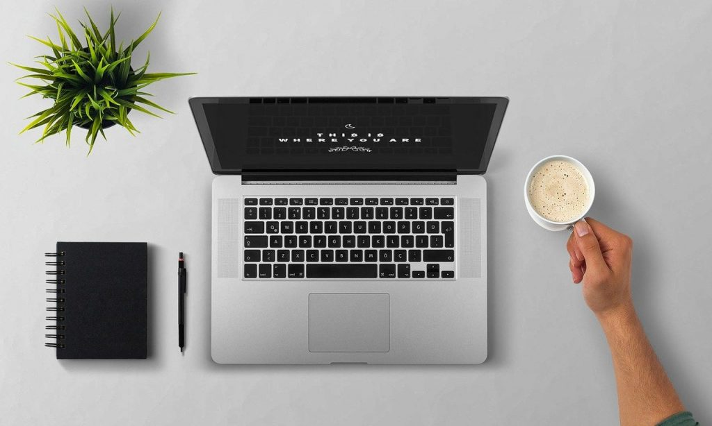 Mesa com notebook, bloquinho de notas e a mão de uma pessoa que segura uma xícara de café.